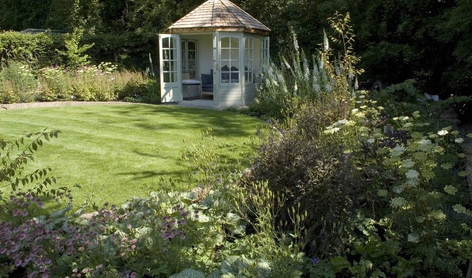 garden uses a woodland edge habitat to advantage for planting and summerhouse